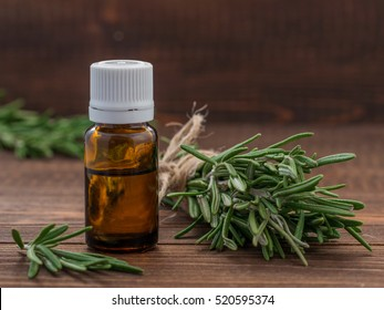 Rosemary essential oil in dark glass bottle and fresh rosemary on dark wooden background with copy space