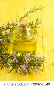 Rosemary essential oil in glass bottle and plant with flowers on yellow wooden background