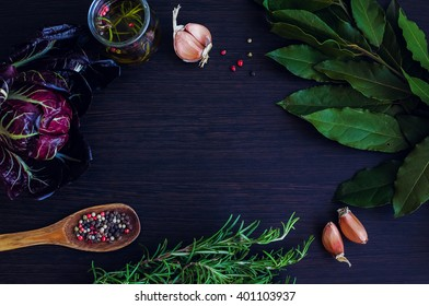 Rosemary, garlic, chicory, Bay leaf, olive oil with spices, wooden spoon with pepper on dark background. Background layout with free text space. Copy space. Top view. Food flat lay.