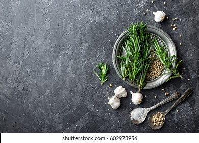 Rosemary, garlic, salt and white peppercorns, culinary background with various spices, directly above, flat lay, copy space
