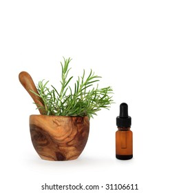 Rosemary herb leaves in an olive wood mortar with pestle and aromatherapy essential oil glass dropper bottle, over white background.