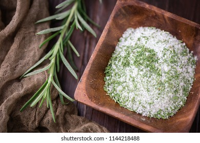 Rosemary Herb Salt in Small Wooden Bowl; Fresh sprig of herb on Wooden Tabletop beside the bowl