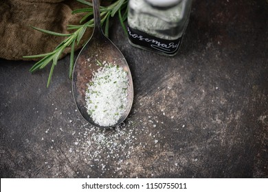 Rosemary Herb Salt in Tarnished Spoon on Black Background with Fresh Sprig of Rosemary