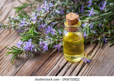 Rosemary herbal essential oil on the wooden background
