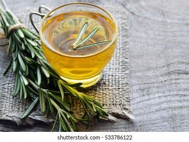 Rosemary herbal tea in a glass cup on rustic wooden background with copy space.Rosemary tea.Selective focus.