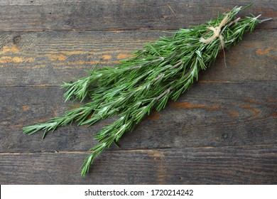 Rosemary herbs on the rough wooden background.  Fresh fragrant plants with evergreen leaves