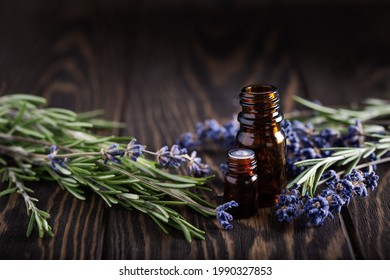 Rosemary and lavender essential oils in dark glass bottles on wooden background,  herbal and floral sprigs with amber jars.