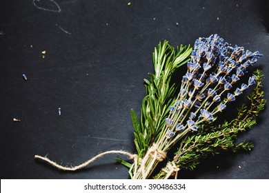 Rosemary, lavender and thyme sprigs tied with string on a dark gray background