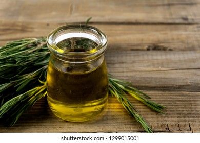 Rosemary oil. Rosemary essential oil jar glass bottle and branches of plant rosemary with flowers on wood background.
