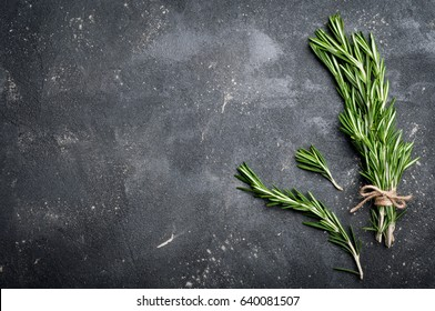 Rosemary on dark concrete table top view. Herbs and spices background. Copy space for your recipe