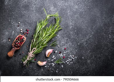 Rosemary, peppercorn and garlic on dark stone or metal table. Ingredients for cooking. Food background. Top view with copy space.