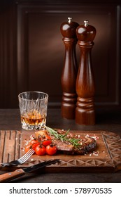Rosemary ribeye steak with cherry tomatoes on a wooden serving board. Flatware, a glass of whiskey, pepper mills. Classic restaurant recipe.