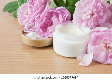 Roses bunch and cosmetic cream on wooden desk. Natural cosmetic concept