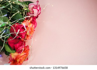 Roses with fairy lights on a pink background