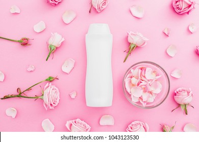 Roses flowers with petals and shampoo on pink background. Beauty female concept. Flat lay, Top view.