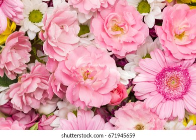 Roses, gerbera and chrysanthemum - colorful flowers arranged as a natural close up background image with white and pink blossoms