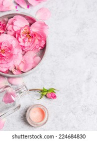 Roses in gray bowl with water , cream and pink bottle with Booth on  stone background