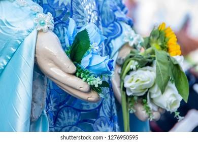 of roses in the hand of iemanja image in Copacabana in Rio de Janeiro Brazil.