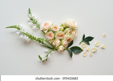 Roses heads on white background. Assorted flowers and leaves scattered on a table with decorative heart shape, overhead view wallpaper. Flat lay, top view. Nice border. Decoration elements.