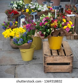 Roses, lilies, hyacinths in buckets on the street on the sidewalk for sale
