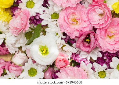 Roses, lisianthus and other colorful flowers arranged as a beautiful natural background  with white, yellow and pink blossoms - close up image