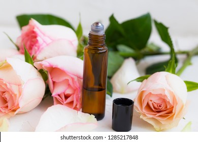 Roses oil perfume in roller bottle with roses flowers, beauty natural rose oil perfume aroma