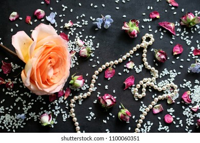 roses, pearl necklace and rice on black background - symbols of a wedding