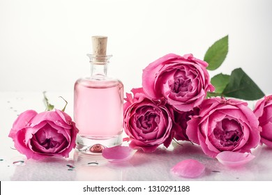 Roses, pink perfume essence in a bottle. Aromatherapy, spa treatments.