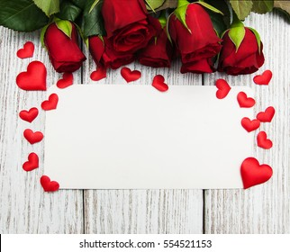 Roses and red  hearts   on a white wooden background