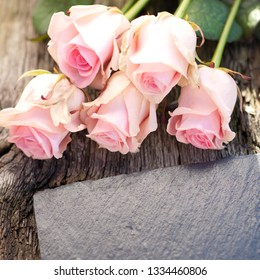 Roses and slate on wooden ground