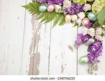 Roses, stock, and hydrangea flowers with easter eggs frame over rustic wooden boards, background for Easter. Copy space.