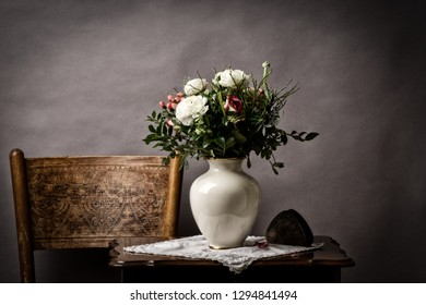 roses in the vase wither on old side table
