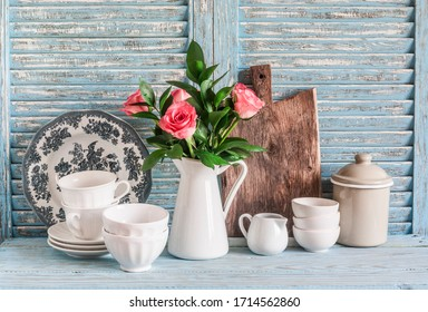 Roses in a white pitcher, vintage crockery on blue wooden rustic background. Kitchen still life in vintage country style. Flat lay