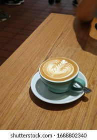 Rosetta latte art on a cup of coffee on wooden table