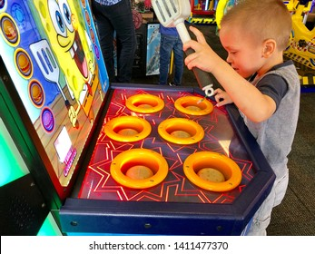 Roseville, CA - May 25, 2019: Toddler playing a Sponge Bob whack a burger arcade game at Chuck E Cheese's.