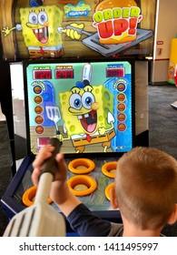Roseville, CA - May 25, 2019: Young boy playing a Sponge Bob Squarepants Order Up Whack A Burger game at Chuck E Cheese.