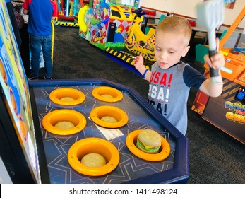 Roseville, CA - May 25, 2019: Boy playing a whack a mole burger game inside Chuck E Cheese.