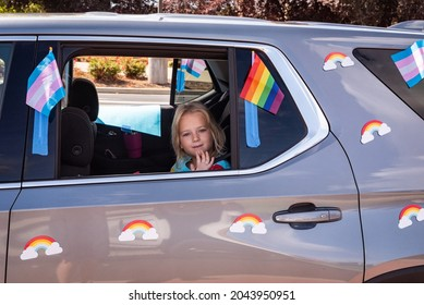 ROSEVILLE, CA, U.S.A. - SEPT. 19, 2021: A small child waves out a window of a car decorated with rainbow and transgender flags as part of Placer County's Pride caravan event.