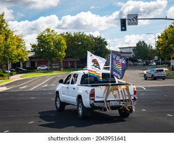 """ROSEVILLE, CA, U.S.A. - SEPT. 19, 2021: A white pickup truck with a """"We the People"""" rainbow flag and California State rainbow flag flying turns during the annual Placer County Pride caravan event."""