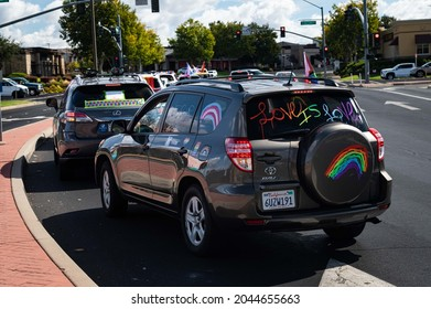 """ROSEVILLE, CA, U.S.A. - SEPT. 19, 2021: An SUV decorated with """"Love is Love"""" on its back windshield drives as part of the  Placer County Pride caravan event."""