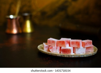Rosewater-flavored Turkish Delight or Rahat Lokum (Loukoumi, Ratluk) on a vintage plate. In the background are two copper vintage cezves and a coffee grinder. Golden background. Front view. Copy space