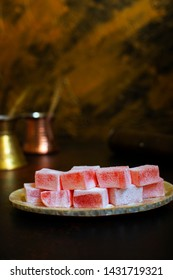 Rosewater-flavored Turkish Delight or Rahat Lokum (Loukoumi, Ratluk) on a vintage plate. In the background are two copper vintage cezves and a coffee grinder. Golden background. Vertical. Copy space