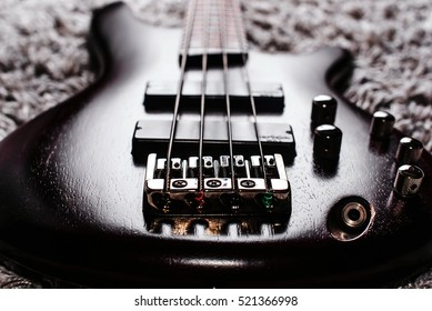 Rosewood bass electric guitar with four strings on the gray carpet closeup