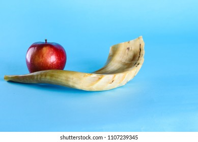 Rosh Ha Shana - Jewish new year composition of an red apple and Shofar horn for Rosh Hashanah on blue background.Jews dip a slice of apple in honey to express hopes for a sweet and fruitful year.
