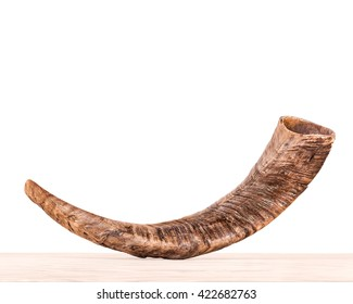 Rosh Hashana holiday shofar on light color wood grain surface, isolated on white background. Side view of textured ram's horn. Jewish New Year religious object. Copy space.