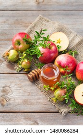 Rosh Hashana, jewish new year holiday concept with traditional symbols, apples, honey, pomegranate on a wooden rustic table. Copy space background