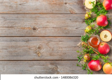 Rosh Hashana, jewish new year holiday concept with traditional symbols, apples, honey, pomegranate on a wooden rustic table. Copy space, flat lay background