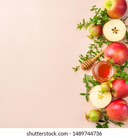 Rosh Hashana, jewish new year holiday concept with traditional symbols, apples, honey, pomegranate on a pastel pink, coral table. Flat lay, copy space background
