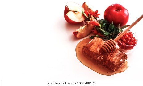 Rosh Hashanah flatlay: honey comb, pomegranate seeds and flowers, apples
