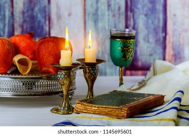 rosh hashanah jewesh holiday concept shofar, torah book, honey, apple and pomegranate. traditional holiday symbols.